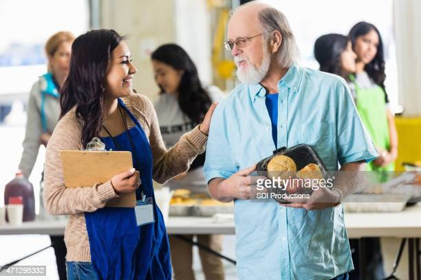volunteer assisting senior man in local food bank for charity - depression bread line stock pictures, royalty-free photos & images