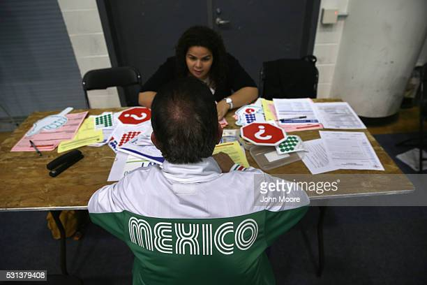 A volunteer assists a Mexican immigrant with his US citizenship application at a Citizenship Now event held by City University of New York on May 14...