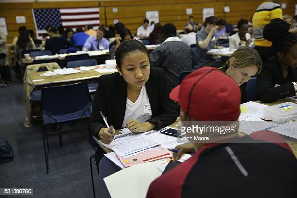 A volunteer assists an immigrant with his US citizenship application at a Citizenship Now event held by City University of New York on May 14 2016 in...