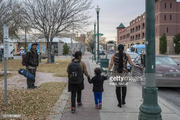 A volunteer assists Central American asylum seekers who were dropped off in downtown El Paso by Immigration and Customs Enforcement on Christmas day...