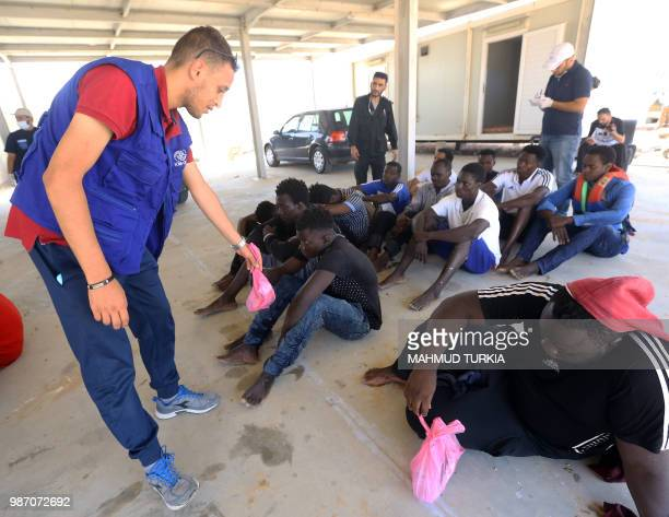 A volunteer assists migrants who survived the sinking of an inflatable dinghy boat off of the coast of Libya arrive on the shore of alHmidiya east of...