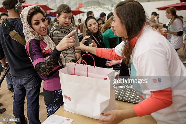 A volunteer at a shelter for migrants and refugees run by the Berliner Stadtmission charity hands out a bag with clothing donated by Japanese casual...