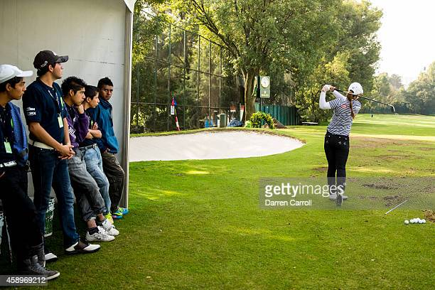 Volunteer attendants look on as Meena Lee of South Korea warms up on the driving range prior to the second round of the 2014 Lorena Ochoa...