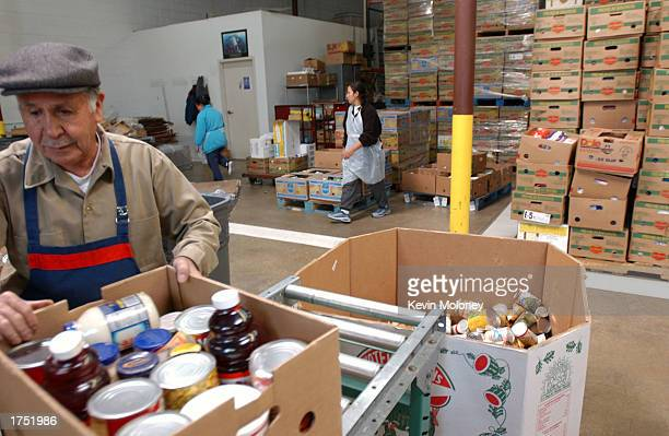 Volunteer Bacilio Sosa and others process donated food at the Food Bank of the Rockies January 29 2003 in Denver Colorado The Food Bank of the...