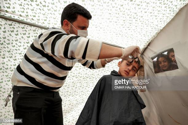 A volunteer barber wearing a surgical mask as a measure against the COVID19 coronavirus pandemic cuts the hair of a child inside a tent at a camp for...