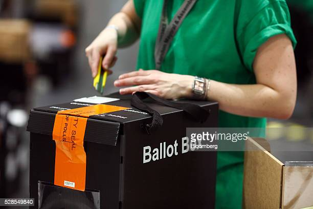 A volunteer breaks the seal on a ballot box during counting for the London Mayoral election at the Excel centre in London UK on Friday May 6 2016...