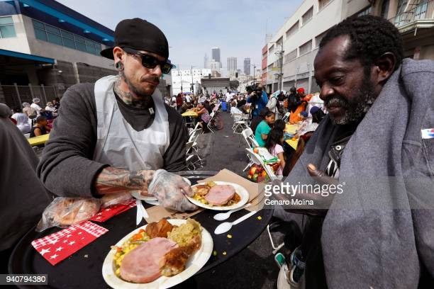 LOS ANGELES CA APRIL 1 2018 Volunteer Brian Burnham left hands out plates of food to hundreds of homeless and nearhomeless men and women and children...