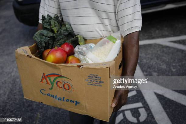 A volunteer carries a box during an event organized by the food bank Feeding South Florida for handout groceries in a drivethru distribution site...
