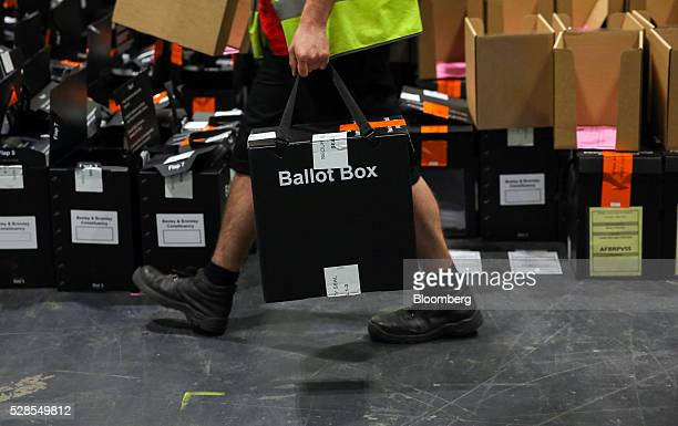 A volunteer carries a sealed ballot box during counting for the London Mayoral election at the Excel centre in London UK on Friday May 6 2016 Sadiq...