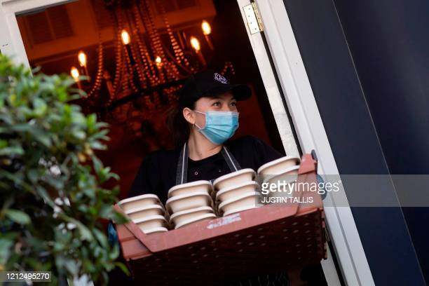 Volunteer carries a tray of prepared free meals to a truck for distribution to NHS staff, key workers and vulnerable people, outside a restaurant in...