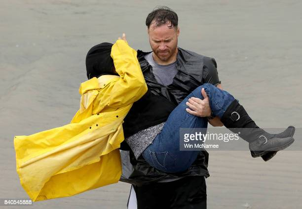 A volunteer carries a woman whose home was impacted by severe flooding following Hurricane Harvey in north Houston August 29 2017 in Houston Texas...