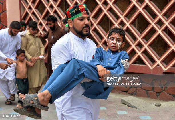 Volunteer carries an injured boy to a hospital, following multiples of bomb blasts in Jalalabad on August 19, 2019. - Afghanistan's independence day...