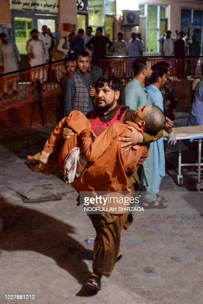Volunteer carries an injured man to hospital, following a bomb blast attack in a prison in Jalalabad city on August 2, 2020. - Armed men stormed a...