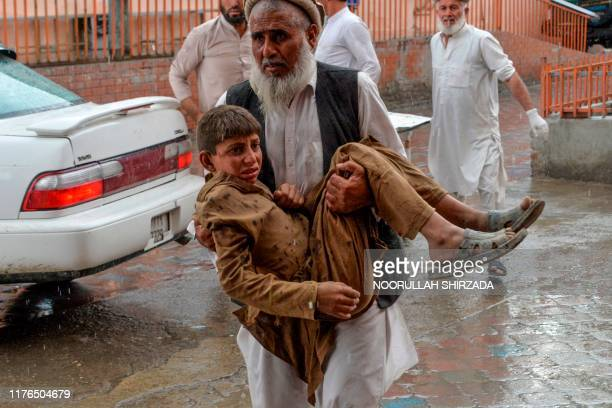 Volunteer carries an injured youth to hospital, following a bomb blast in Haska Mina district of Nangarhar Province on October 18, 2019. - At least...
