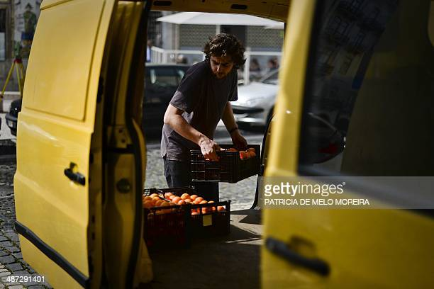 A volunteer carries boxes of fruit from a van at the Fruta Feia in Lisbon on March 17 2014 The coop was created over the last year with the objective...