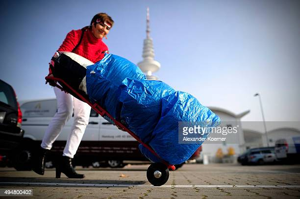A volunteer carries clothes towards a huge donations center for migrants and refugees at the Messe trade fair grounds on October 29 2015 in Hamburg...