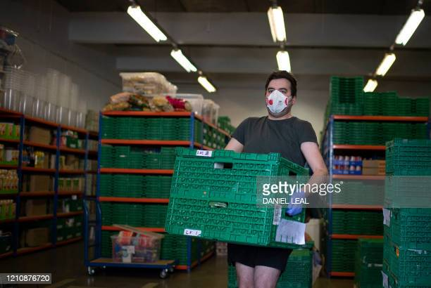 A volunteer carries crates packed with goods for distribution to families inside the First Love foundation foodbank warehouse in Tower Hamlets in...