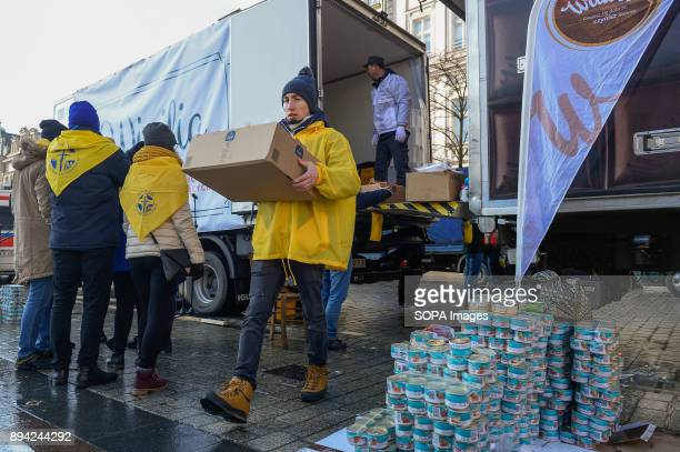 A volunteer carries food suplies as he takes part in the 21st Edition of the Biggest Christmas table in Europe at the Main Square in Krakow The so...
