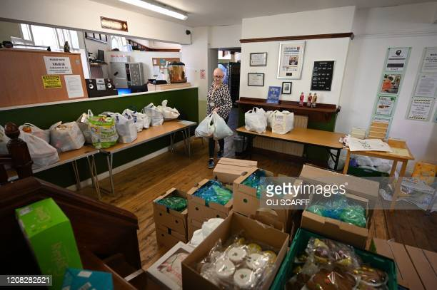 A volunteer carries packed pags of food inside a Trussell Trust food bank in Oldham northwest England on March 26 2020 Panicbuying due to the...