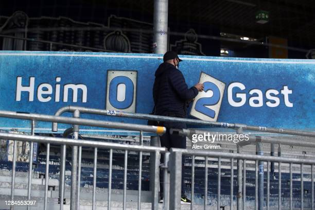 Volunteer changes the score on the analog score board from 0-2 to 0-3 after Dennis Srbeny of Paderborn scored his team's third goal during the Second...