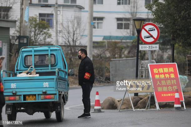 Volunteer checks a driver into a village in Hangzhou in east China's Zhejiang province Monday, Feb. 03, 2020.- PHOTOGRAPH BY Feature China / Barcroft...