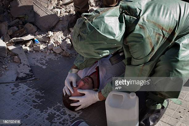 A volunteer checks a man's pupils as he takes part in a simulation of how to respond to a chemical attack in the northern Syrian city of Aleppo on...