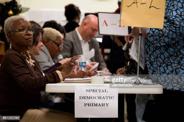 A volunteer checks off voters as they arrive at the Beulah Baptist Church polling station in Montgomery AL on December 12 2017 Alabama voters were...