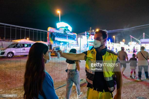 Volunteer checks the temperature of the people entering the Luna Park, on the first day of the opening of the Luna Park in Molfetta on 4 September...