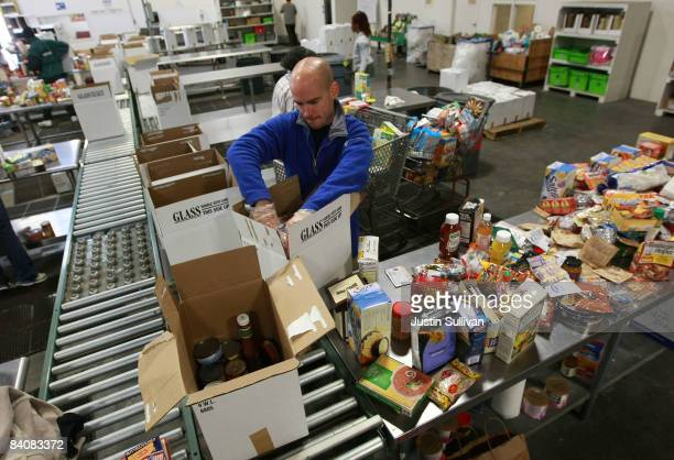 Volunteer Christopher Lindstrom packs boxes of food for needy families at the Alameda County Community Food Bank December 18 2008 in Oakland...