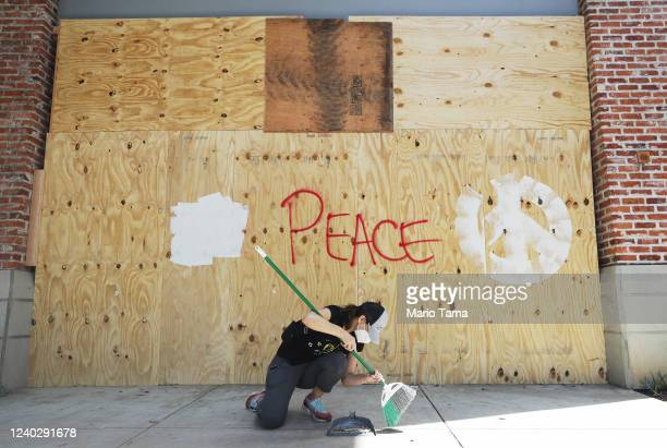 A volunteer cleans in front of a shop window boarded up a day after looting occurred amid protests on June 01 2020 in Santa Monica California...