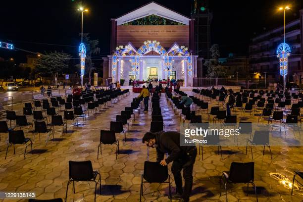 A volunteer cleans the chairs for the faithful who will attend the first mass of the Santi Medici in Bitonto in the square in front of the Basilica...