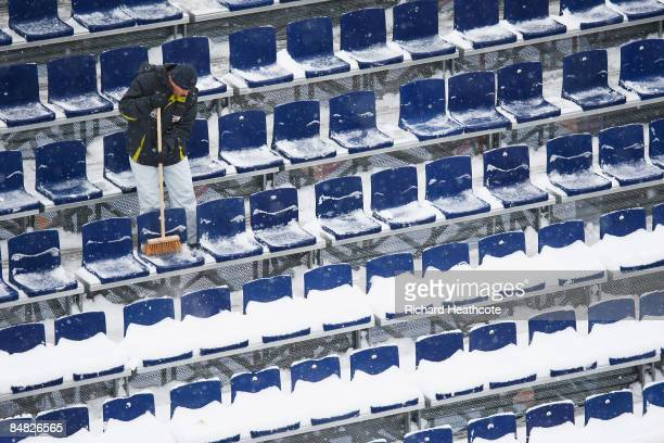 Volunteer clears the snow from the grandstand at the Jested Ski Jumping venue ahead of the FIS Nordic World Ski Championships on February 17, 2009 in...