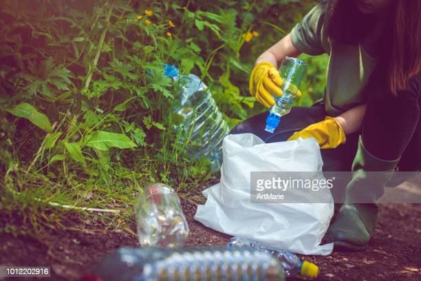 vrijwilliger verzamelt plastic flessen buitenshuis - plukken stockfoto's en -beelden