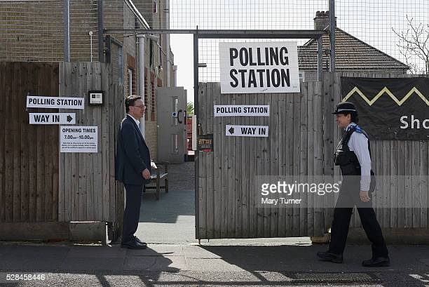 Volunteer Conservative Party teller Mark King talks to a local PCSO outside the polling station at Menorah Primary School in Golders Green North...