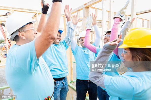 Volunteer construction crew cheers before starting job