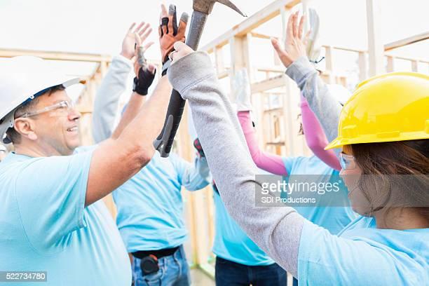 Volunteer construction crew high-five before starting job