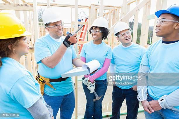 Volunteer construction foreman talks to volunteers