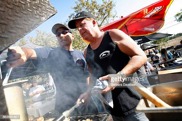 Volunteer cooks Arnie Arii and Brad Cook grill up some chicken and burgers at the Annual Holy Jim Fire Dept Harvest Festival Auction at Cooks Corner...