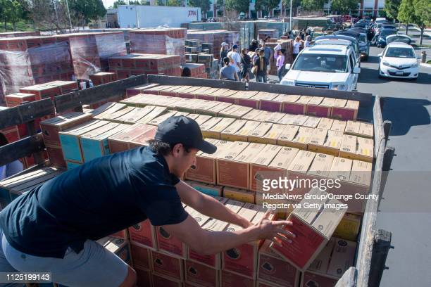 Volunteer Corey Anesi of Cypress helps stack Peanut Butter Patties in the back of a truck for Fullerton/La Habra Troop 2662 during the Girl Scout...