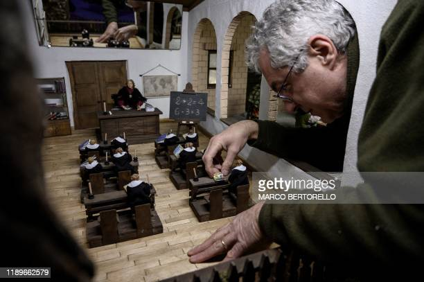 Volunteer Dario Assie sets nativity figures for the 43rd edition of the Presepio of Cavallermaggiore a 300sqm Christmas Nativity crib in the Oratorio...