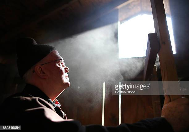 Volunteer David Rice watches the steam escape from the sugar shack where maple sugaring takes place at the Moose Hill Wildlife Sanctuary in Sharon MA...
