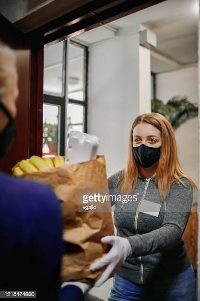volunteer delivering food to elderly people during lockdown - food delivery foto e immagini stock