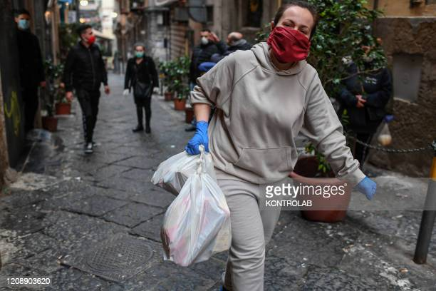A volunteer delivers a package of basic necessities with primary products for the poor people in the popular neighborhoods of Naples city Organized...