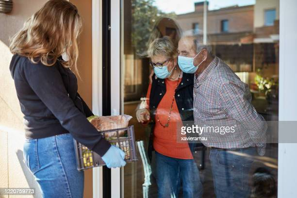 volunteer delivers groceries to senior couple during pandemic - community support stock pictures, royalty-free photos & images