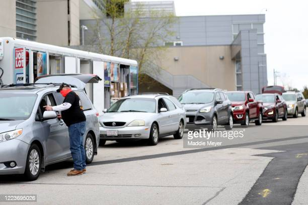 A volunteer directs a line of cars to receive boxes of food as part of the SoupR Bowl at Gillette Stadium on May 08 2020 in Foxborough Massachusetts...