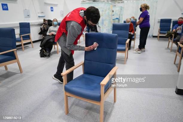 Volunteer disinfects a seat in the post vaccine observation area as Covid-19 vaccines are administered at the NHS Nightingale North East hospital on...