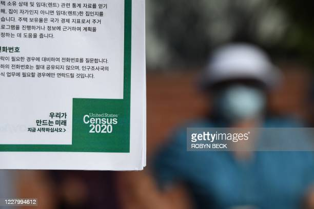 Volunteer displays information in Korean encouraging people to complete the US Census, at a food distribution bank for people facing economic...