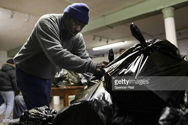A volunteer distributes bags of food at the food pantry at St Augustine's Church on March 15 2010 in the Bronx borough of New York City The St...