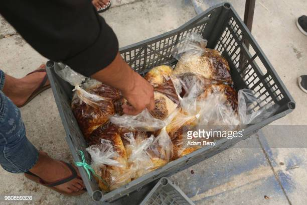 A volunteer distributes bags of hot beans and rice at an independent NGOrun food distribution center outside the Moria refugee camp on May 20 2018 in...