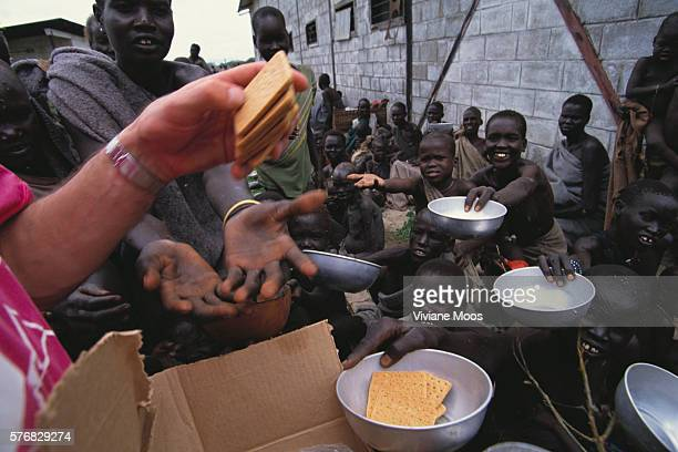 A volunteer distributes crackers to refugees at a feeding center in Kongor Sudan